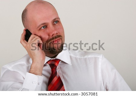 A man in shirt and tie reading a file and talking on mobile phone - stock photo