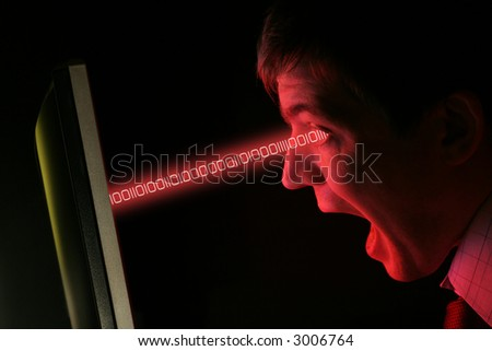 A man in shirt and tie screams at a red computer monitor data streams into his eyes - stock photo