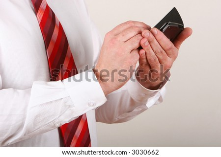 A man in shirt and tie writing on a pda - stock photo