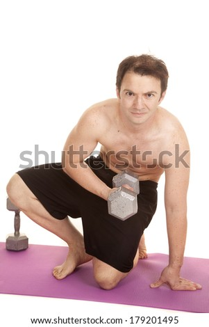 A man in shorts holding a weight kneeling doing a curl. - stock photo