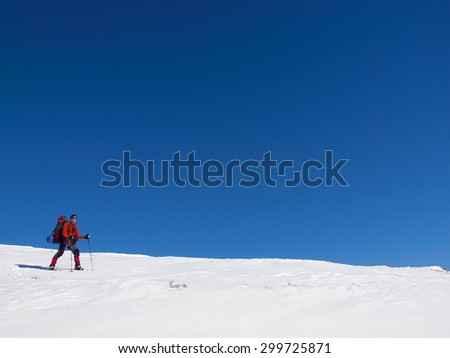 A man in snowshoes with a backpack and goes through the snow.