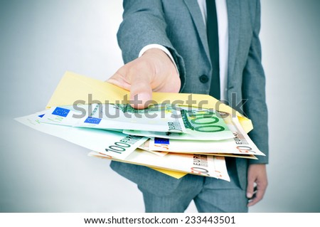 a man in suit giving an envelope full of euro bills - stock photo