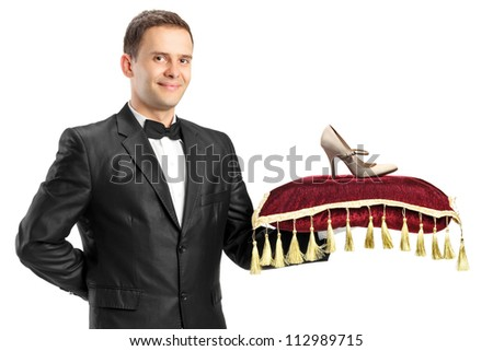 A man in suit holding a pillow with a shoe on it isolated on white background