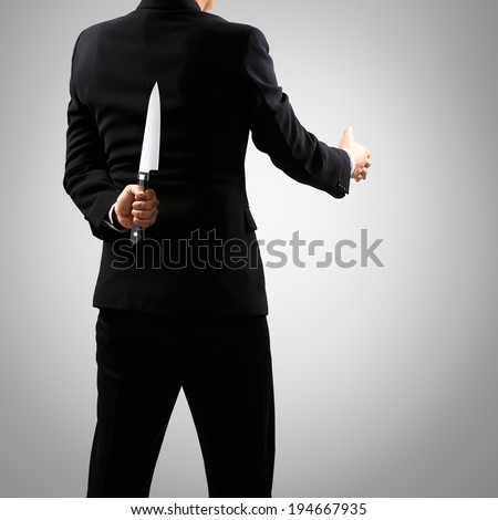 A man in suit holding knife behind back, Isolated on grey background - stock photo