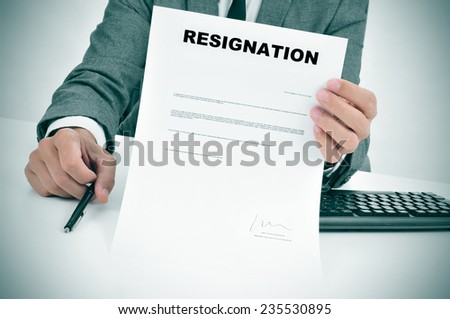 a man in suit in his desk showing a figured signed resignation document - stock photo