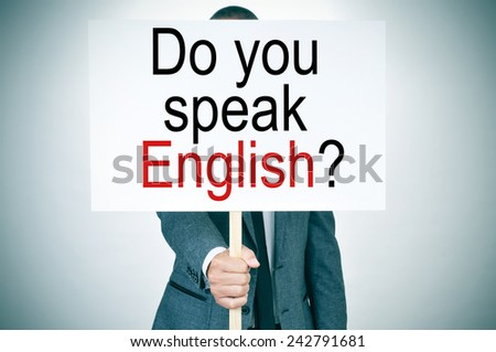 a man in suit showing a signboard with the sentence do you speak english? written in it - stock photo