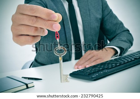a man in suit sitting in an office desk giving the key to the observer - stock photo