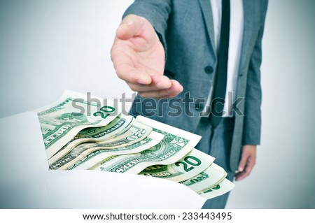 a man in suit taking an envelope full of dollar bills - stock photo