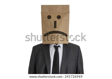 A Man in suit with a paper bag with sad smiley on his head isolated on white background - stock photo