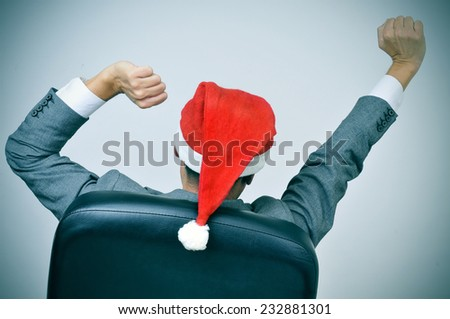 a man in suit with a santa hat stretching his arms in his office chair - stock photo
