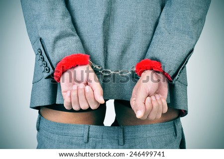 a man in suit with his wrists locked in the back with sexy fluffy handcuffs and his pants down - stock photo