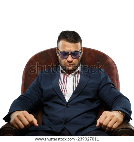 A man in sunglasses sitting in an armchair - stock photo