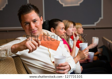 A man in the audience of a theater, in a concert hall or a cinema presenting a ticket or admission pass - stock photo