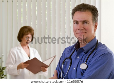 A man in the foreground wearing a stethoscope and a woman in a lab coat out of focus in the background. - stock photo