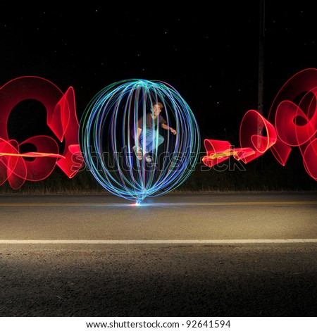 A man in the road at the middle of the night jumping in the middle of an orb