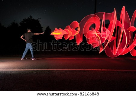 A man in the road at the middle of the night shooting out a graffiti-like artistic laser blast powers from his hand