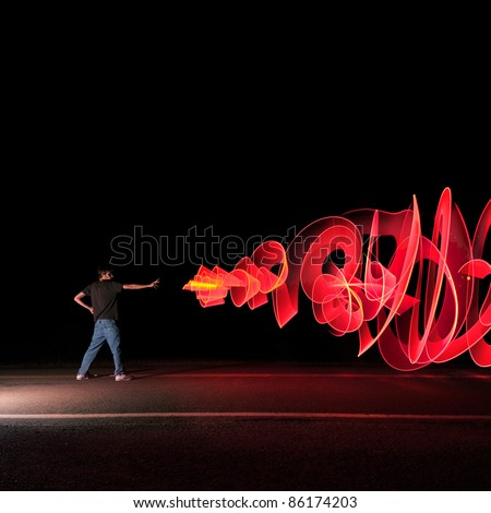 A man in the road at the middle of the night shooting out a graffiti-like artistic laser blast powers from his hand - stock photo
