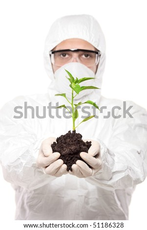 A man in uniform holding a pepper plant isolated on white background - stock photo