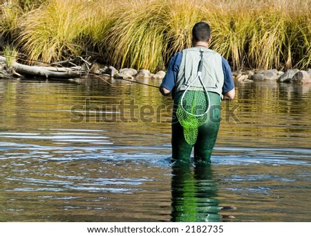 A man in waders fly fishes in a mountain stream. - stock photo