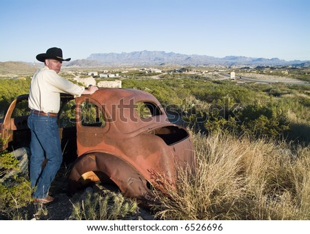 A man in western attire leaning on an old, long abandoned vehicle surrounded by rugged terrain. - stock photo