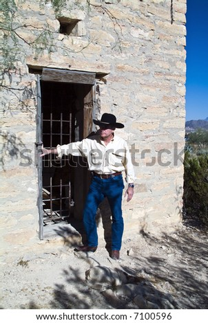 A man in western attire standing outside an old ruin of a jail - stock photo