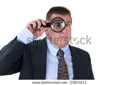 A man inspects things with his magnifying glass, which shows his enlarged eye.