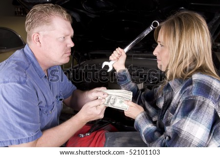A man is angry with the mechanic and doesn't want to give her money, while she is holding a wrench with an angry expression on her face in front of a car engine. - stock photo