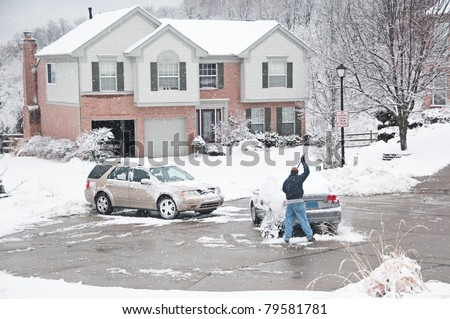 A man is brushing snow off a car during a winter snowstorm in the middle of the street in a suburban neighborhood. - stock photo