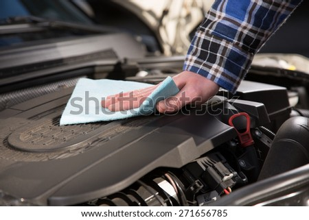 A man is cleaning a car engine block. - stock photo