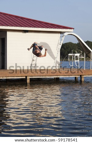 A man is doing a back flip off the end of a dock into the water - stock photo