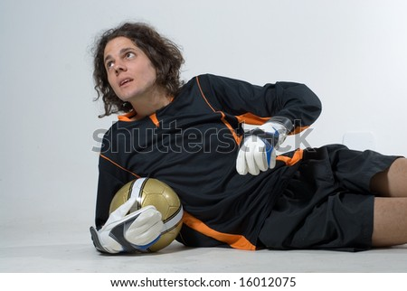 A man is dressed in a soccer uniform and posing in a studio.  He is holding a soccerball and looking away from the camera.  Horizontally framed shot. - stock photo