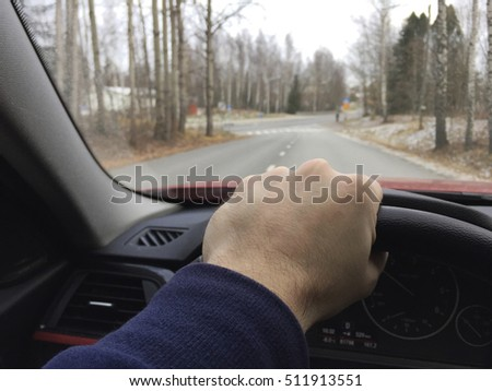 A man is driving a modern car with one hand holding the steering wheel. Focus point on the hand.