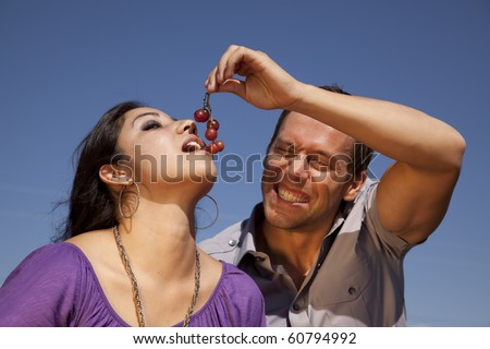 A man is feeding a woman some red grapes in front of a blue sky. - stock photo