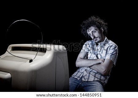 a man is getting bored while watching tv alone - stock photo