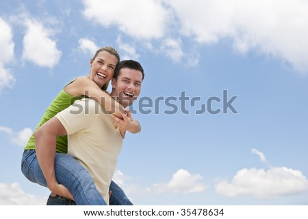 A man is giving a piggy back ride to a woman.  They are both smiling at the camera.  Horizontally framed shot.