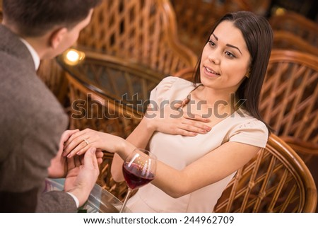 A man is giving a ring as a gift to a female in an outdoor cafe. - stock photo