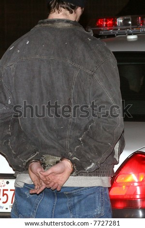 A man is handcuffed by polices. - stock photo