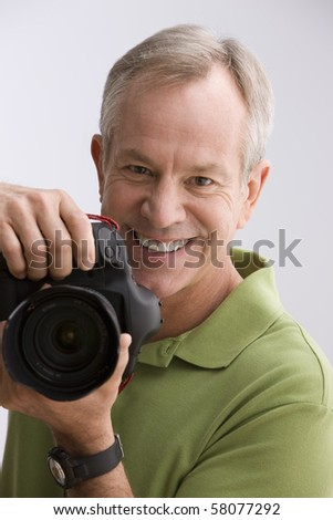 A man is holding a camera as he gets ready to take a photograph. Vertical shot. - stock photo