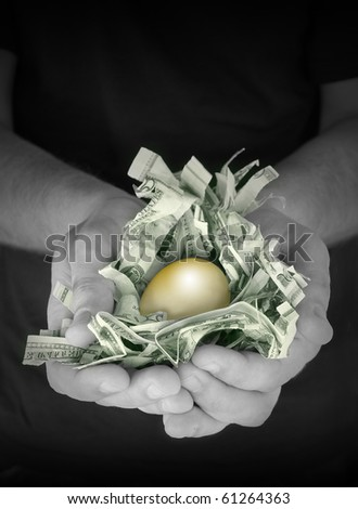 A man is holding a golden nest egg. There is shredded american money and a gold egg on top. Use it for a savings, financial security or retirement concept.