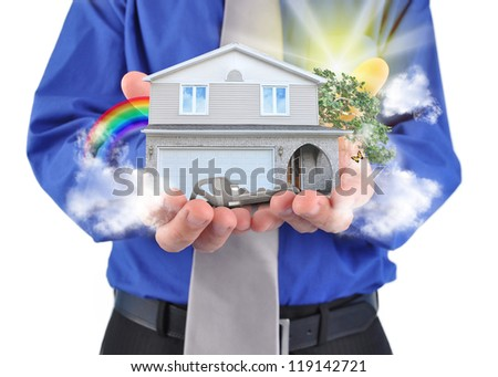 A man is holding a house in his hands with a rainbow and clouds. There is a key for the home ownership. - stock photo