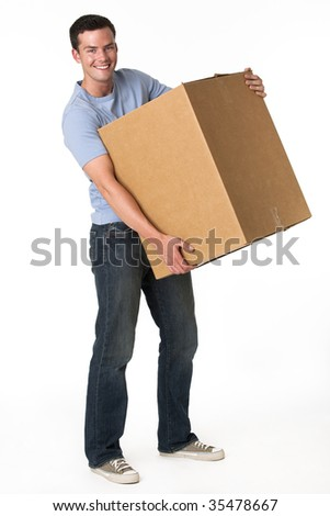 A man is holding a moving box and smiling at the camera.  Vertically framed shot.