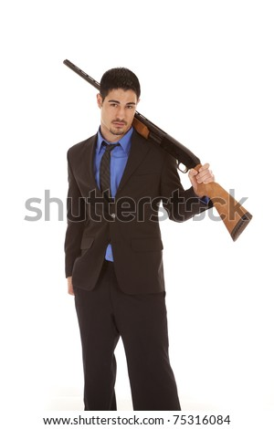 A man is holding a shotgun over his shoulder - stock photo