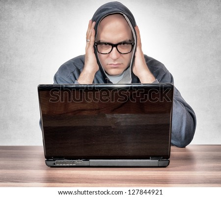 A man is holding his head and looking at the laptop