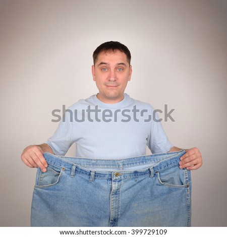 A man is holding up a pair of big large pants for a before and after weight loss concept. He is isolated on the background. - stock photo