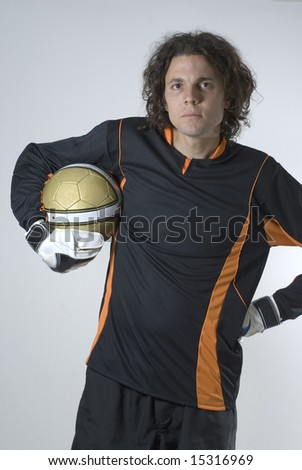 A man is in a studio posing with a soccer ball.  He is wearing a goalie uniform and looking at the camera sternly.  Vertically framed shot. - stock photo