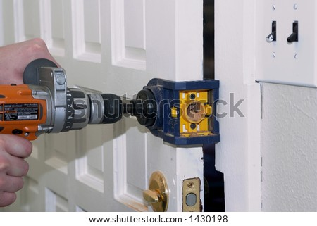 A man is installing a dead bolt for added security - stock photo
