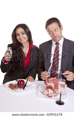 A man is looking at a woman's food.  The woman is looking and smiling. - stock photo