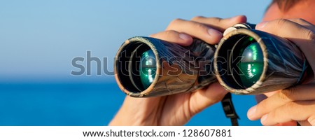 a man is looking to the binocular on sea - stock photo