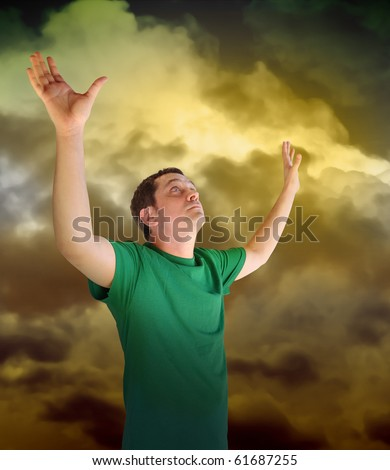 A man is looking up reaching his hands out into the sky representing religion, peace or God. The clouds are yellow. Can also be used for triumph, victory or courage theme.
