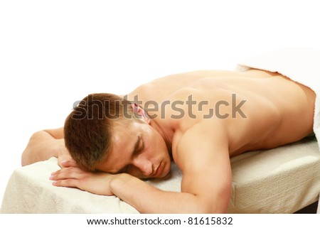 A man is lying and relaxing in spa center isolated on white background - stock photo